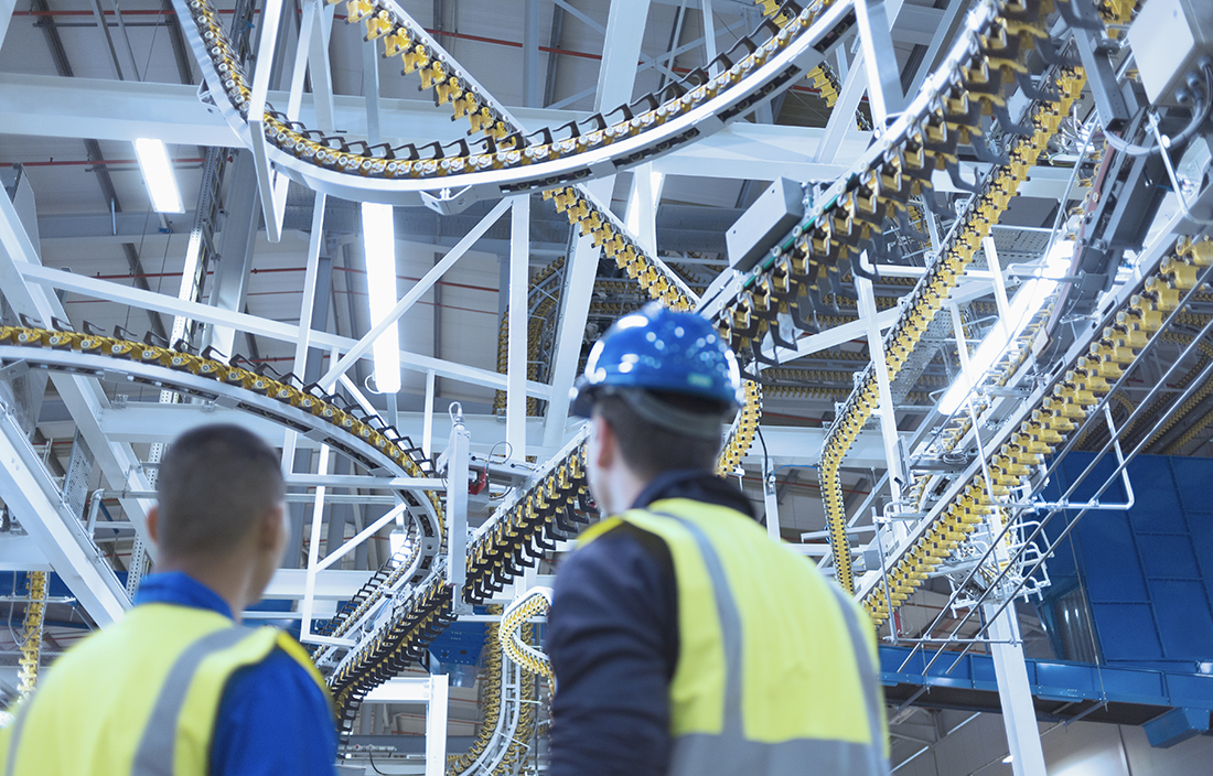 Workers looking at a manufacturing conveyor belt.