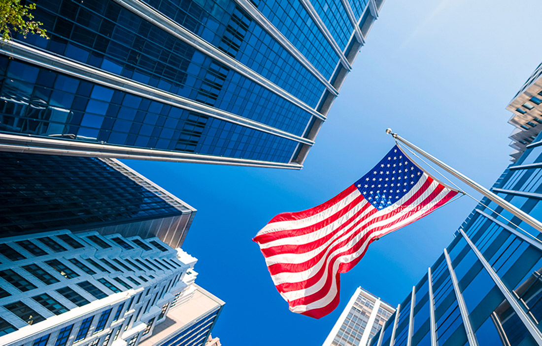 Photo of a U.S. flag nearby tall buildings.