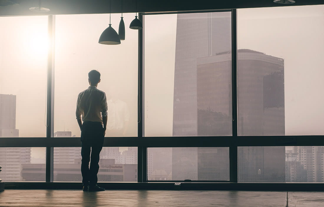 Image of a man looking out of large office windows, onto a misty city morning.