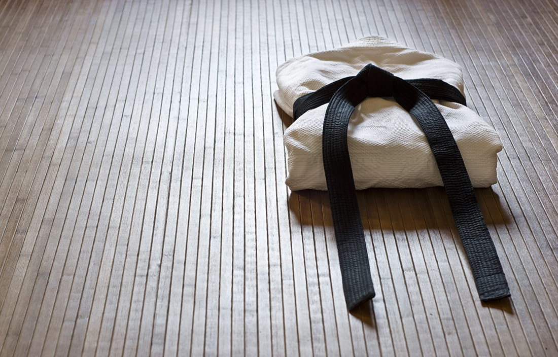 Photo of a martial arts bleck belt on a wooden floor.