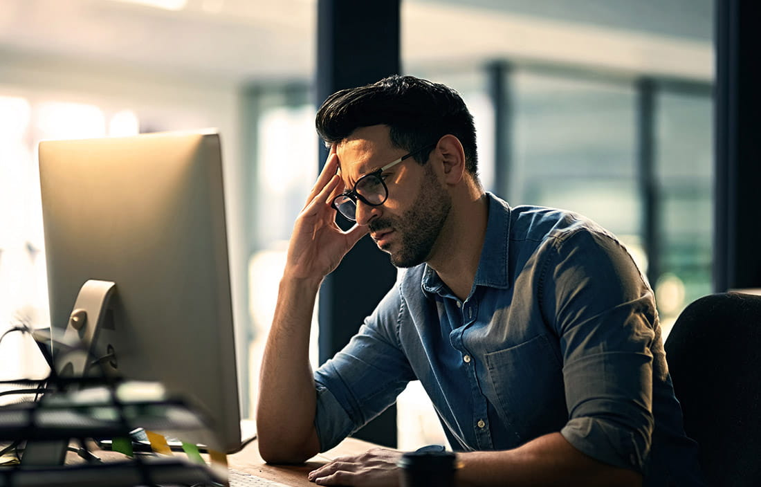 Image of frustrated man in front of computer