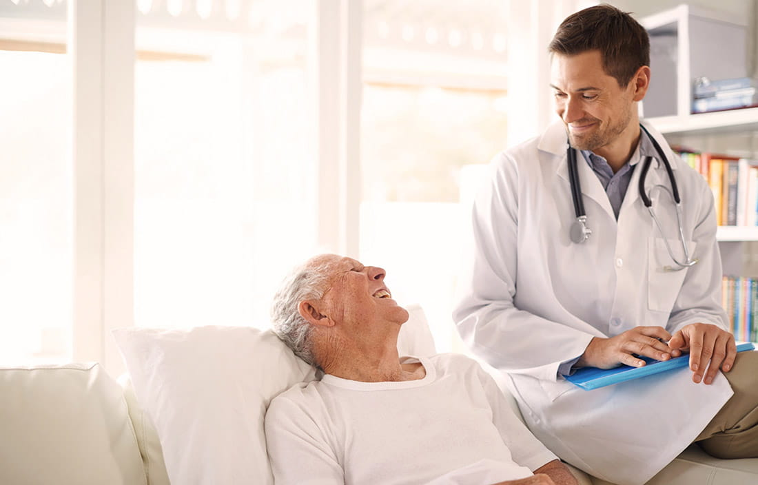 Image of elderly man in hospital bed with a male doctor sitting on the edge smiling down at him; SNF interrupted stay PDPM.