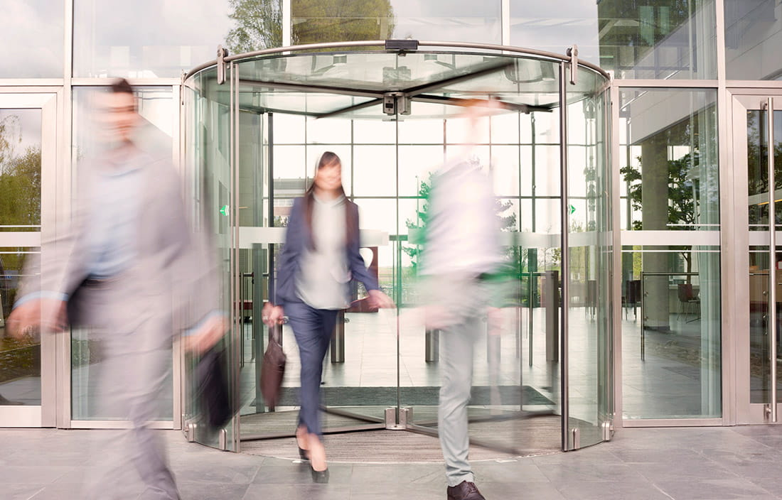 Image of people walking out of revolving doors