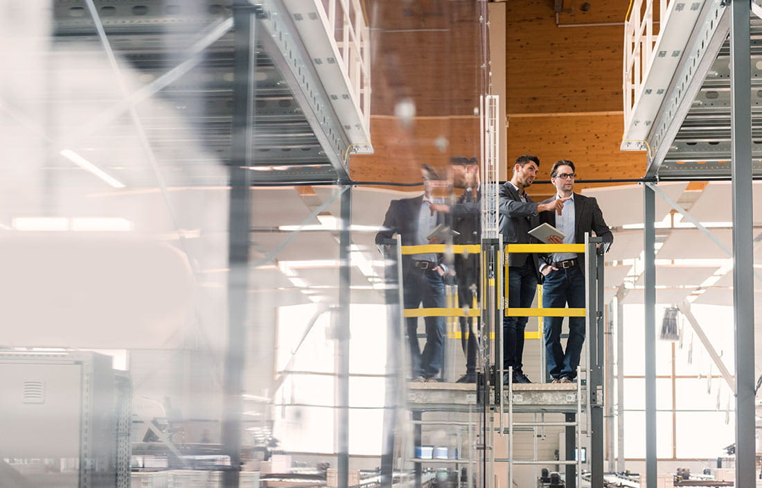 Two business colleagues on a scaffold in a warehouse examining shelving units.