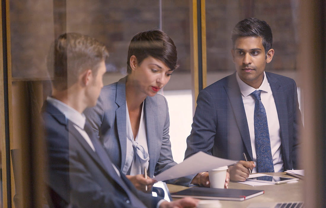 Image of business people having conversation over piece of paper