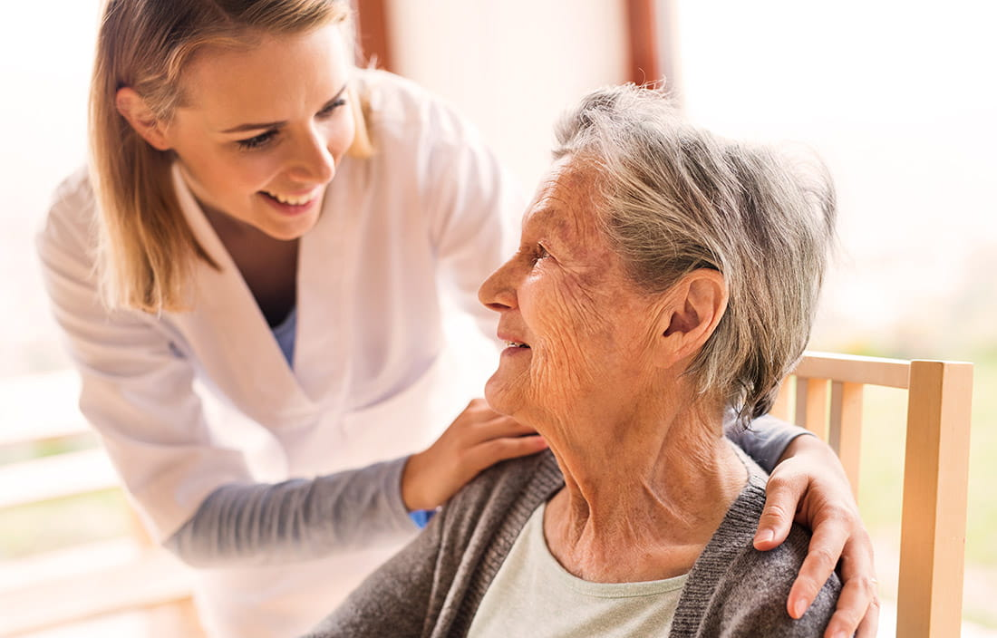 Image of a female nurse leaning over a smiling elderly woman.