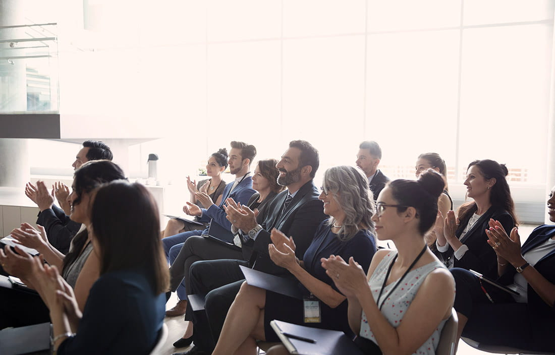 people clapping at a conference