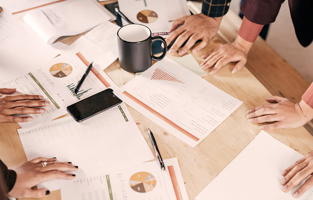 Image of hands on table full of business papers and a coffee mug.