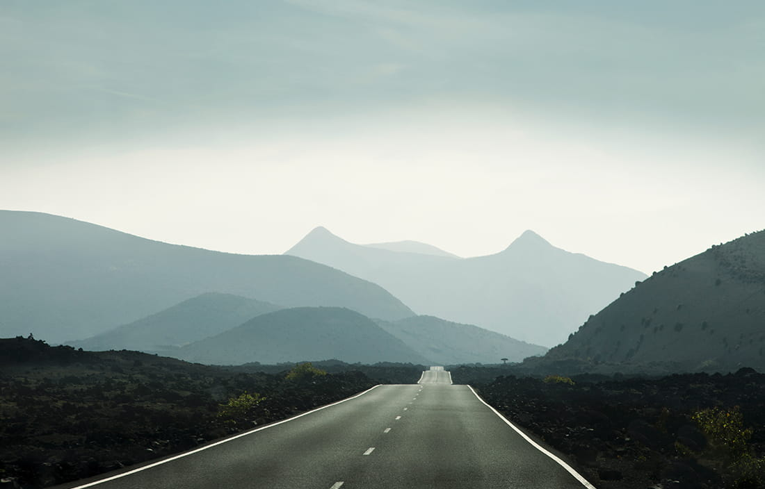Image of a two-lane road heading mountains in the distance.