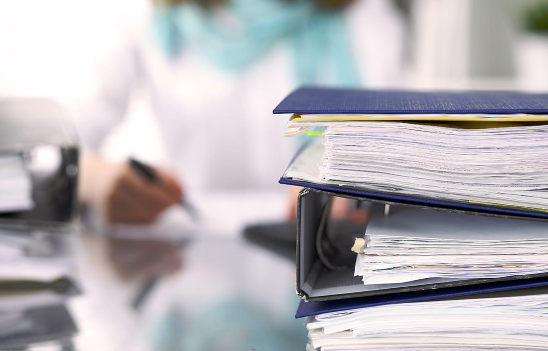 View of a stack of binders and business papers on top of a desk.
