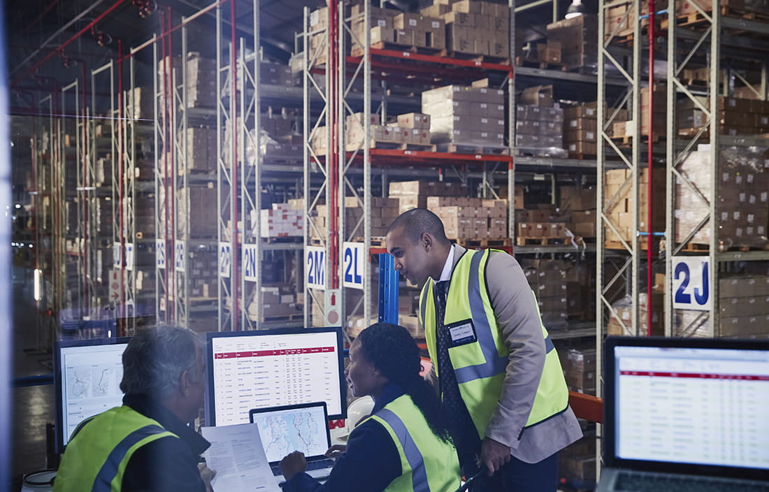 A group of warehouse/manufacturing workers nearby computer monitors.