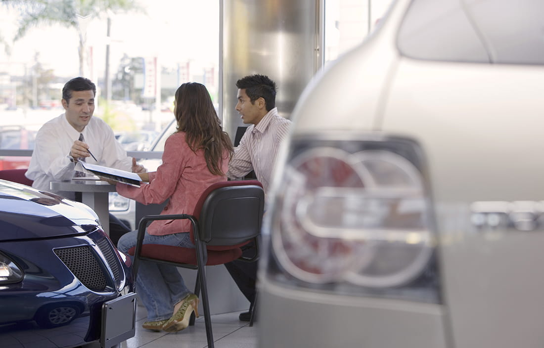 Dealership tax reform discussed by three people at a desk