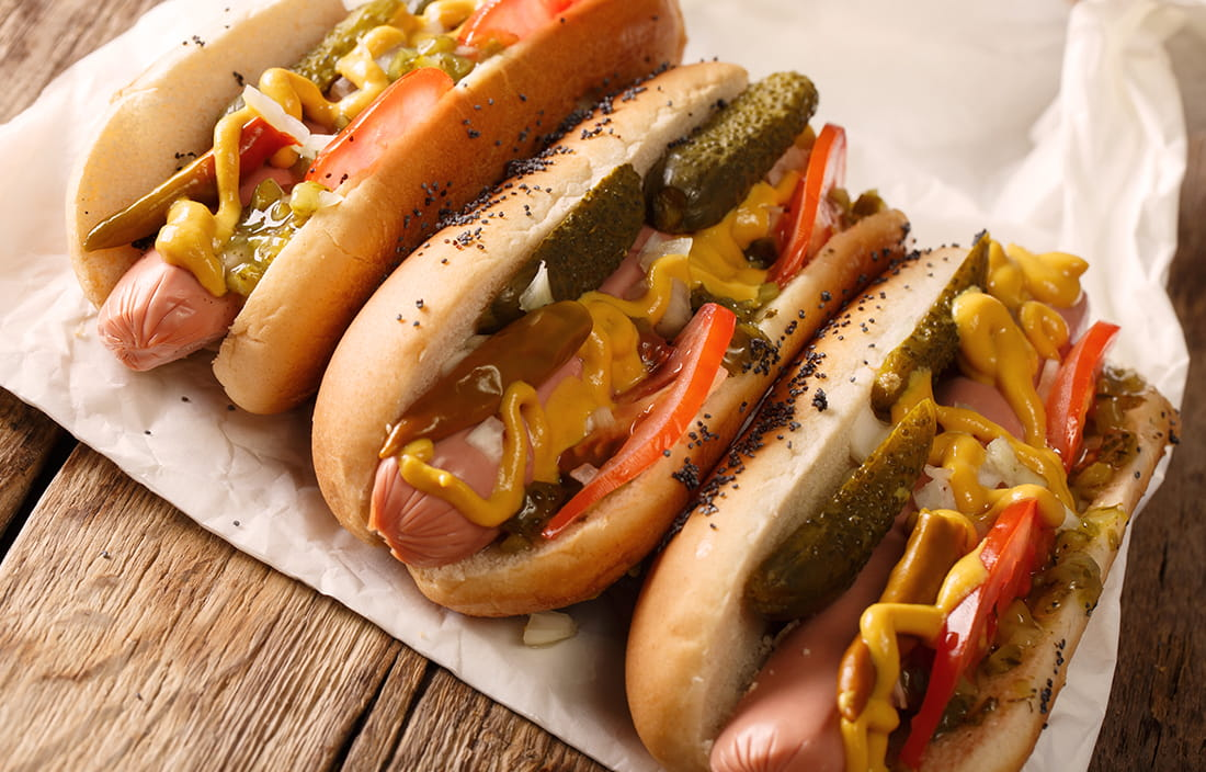Image of three Chicago style hotdogs on paper.