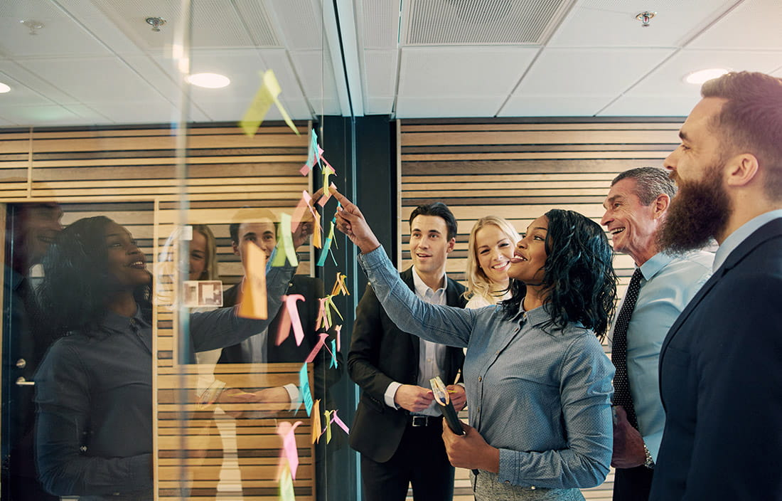 Image of a group of business people looking at multiple colored post-it notes adhered to a glass wall.