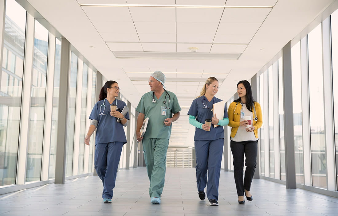 Four physicians and doctors walking down a glass hallway corridor.