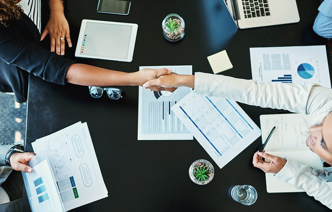 Business colleagues shaking hands while sitting at a conference table.