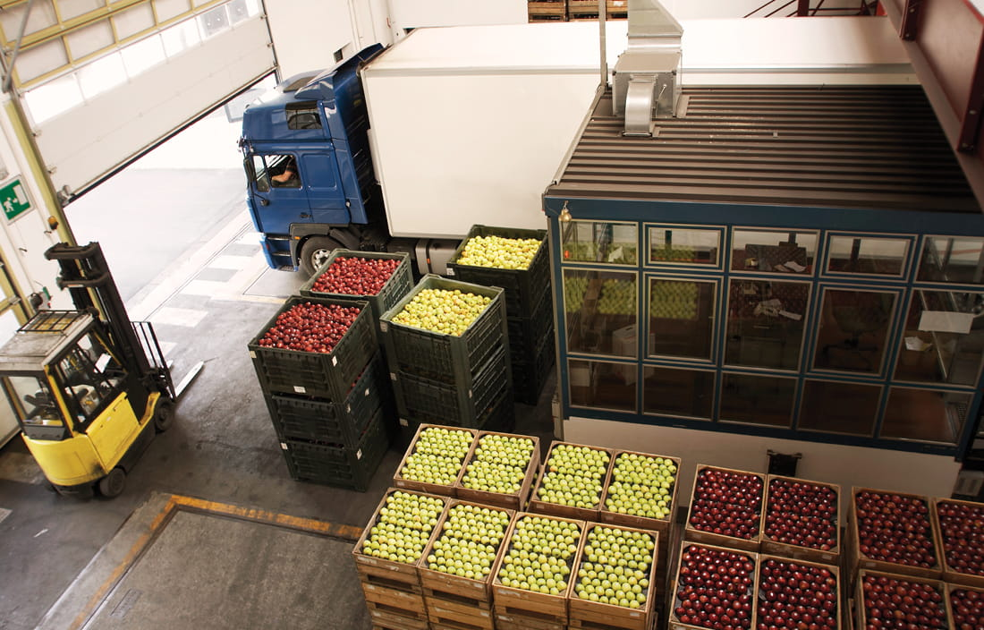 Interior of a warehouse with a shipping truck next to cartons and pallets of apple produce shipments.