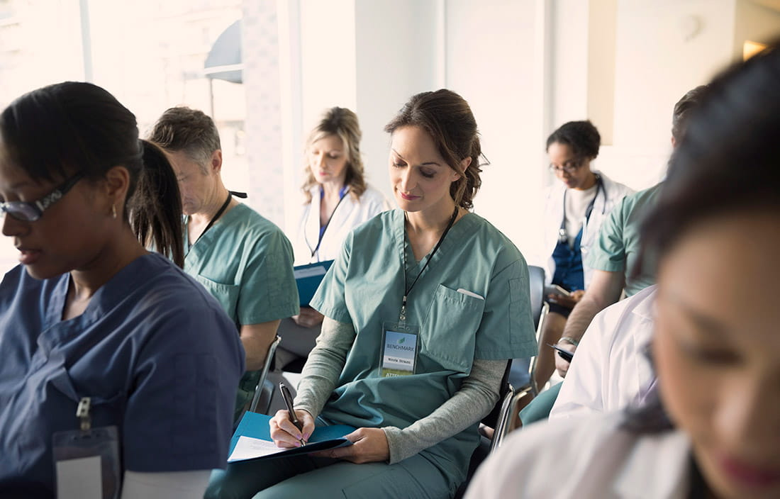 Group of nurses and doctors sitting together reviewing notes.