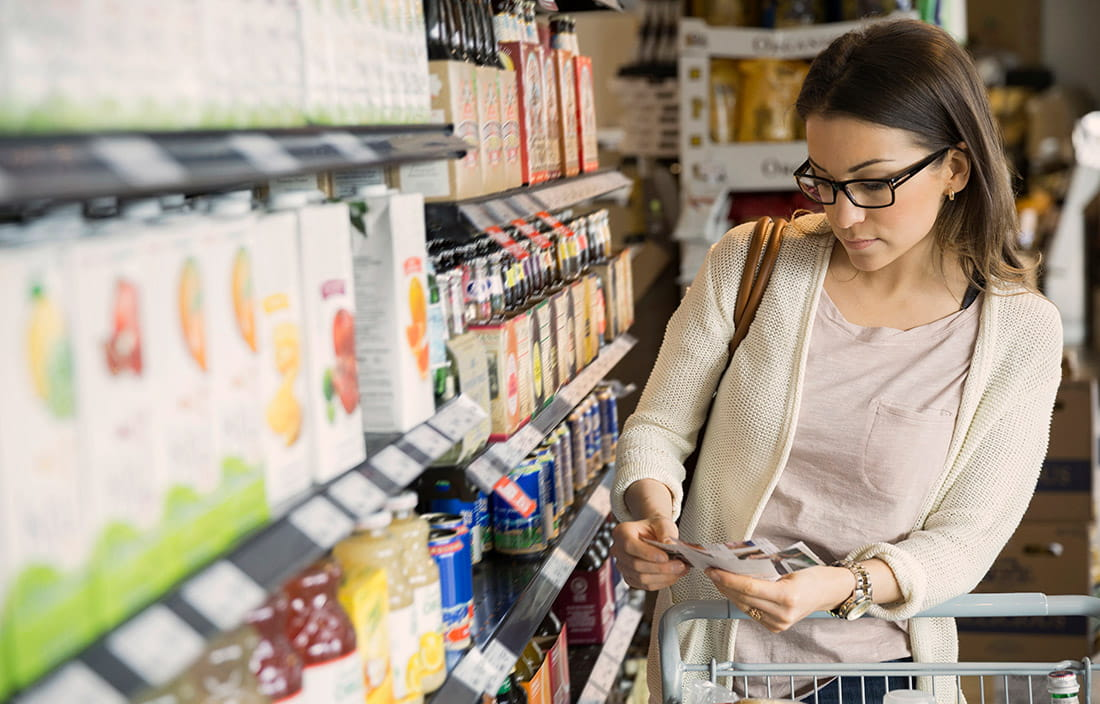 woman looking at products in grocery store aisle