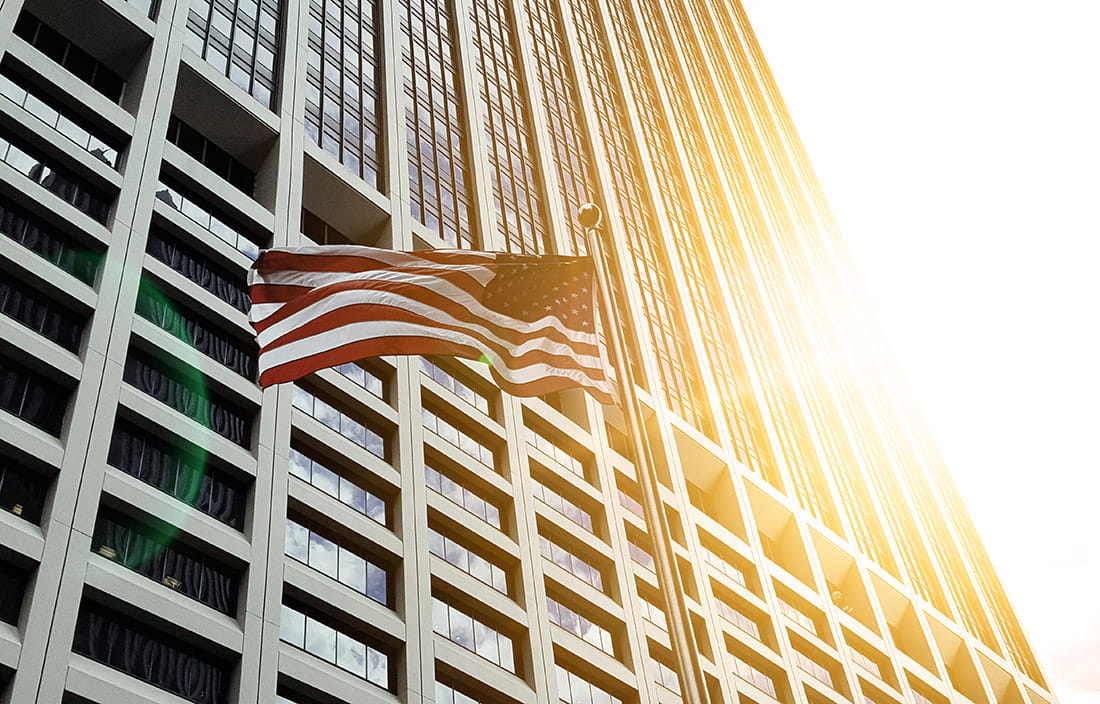 Image of American flag flying in front of a skyscraper.