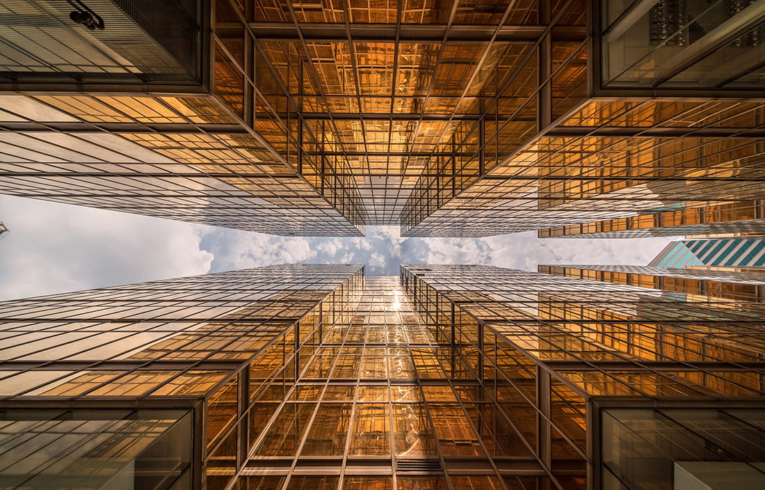 Image of gold skyscrapers from the ground perspective looking up to the sky.