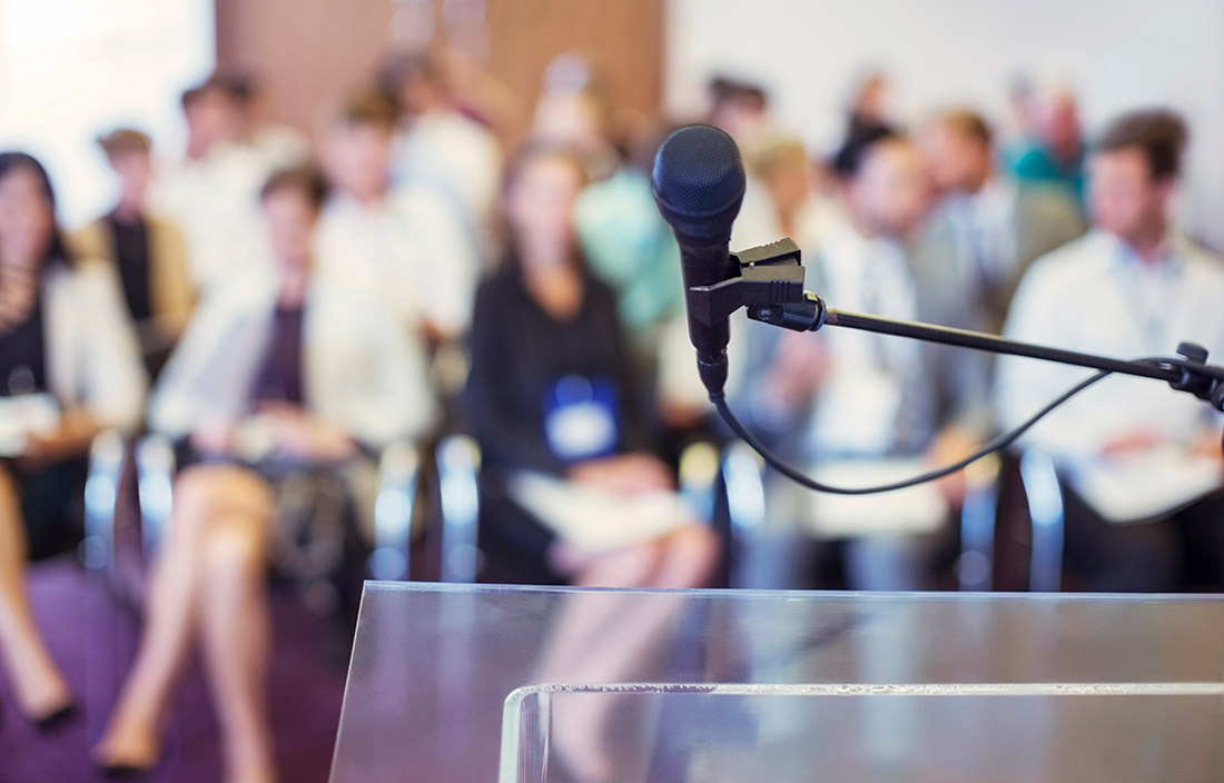 microphone in front of a room full of people