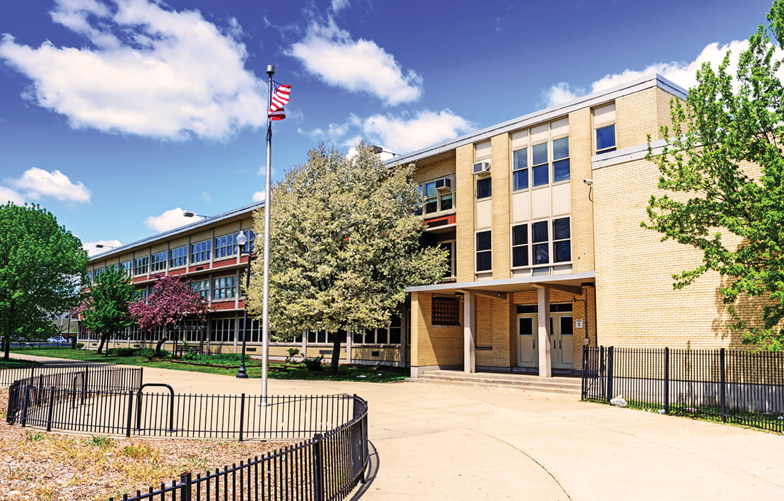 Three-story school building with an American flag in the front courtyard.