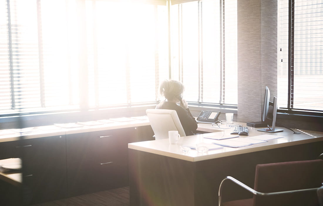 A businesswoman sitting at her desk looking out an office window flooded with sunlight.