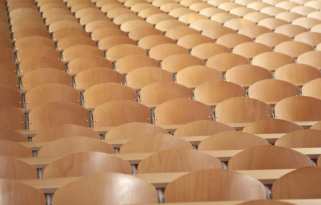 Empty wooden chairs in a lecture hall in a school.