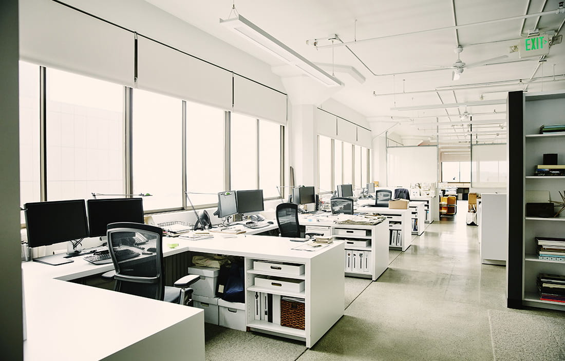 An empty modern office during the day with desk on the left hand side lining the window.