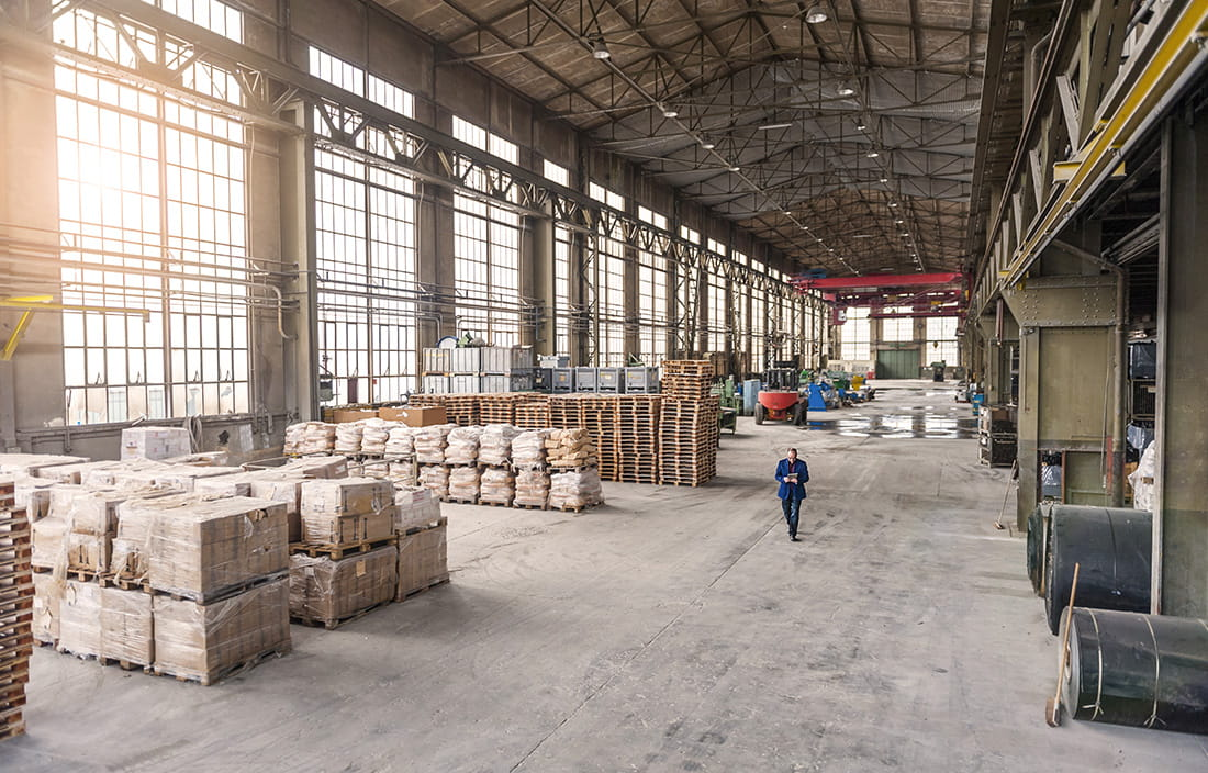 Photo of a warehouse with loading docks and workers walking around.