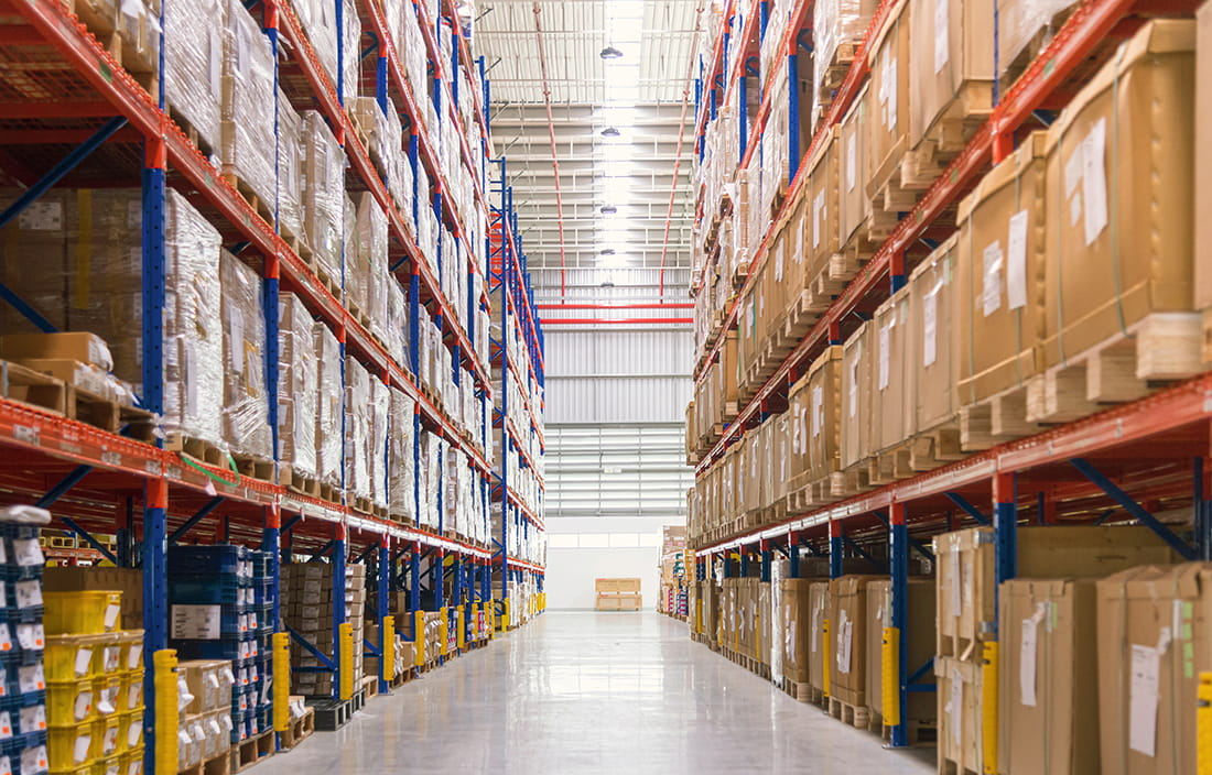 A vantage point of a warehouse aisle with shelving on each side.