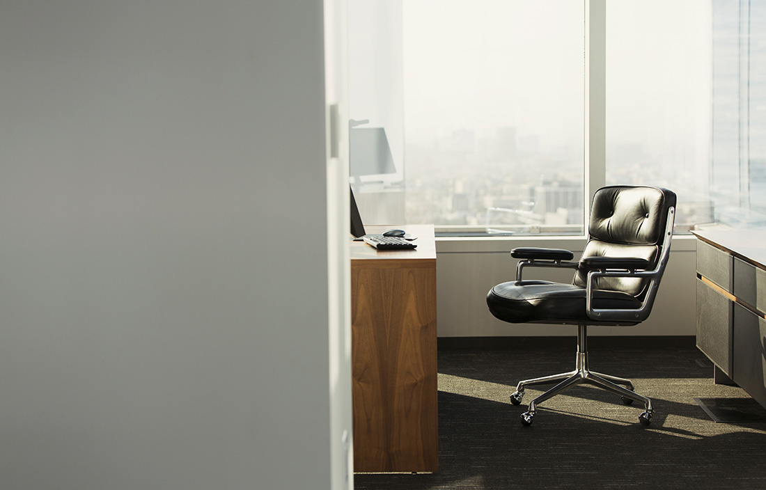 View of an office doorway with a black leather chair in the sunlight.