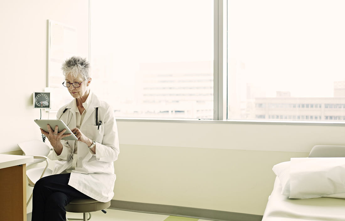 Physician in a treatment room sitting on a stool browsing on her tablet device.