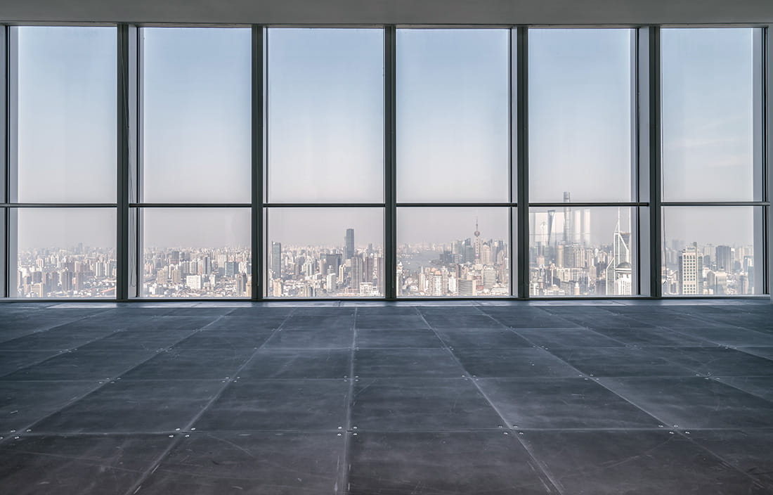 Empty and bare office space with a view of windows looking out at a city skyline.