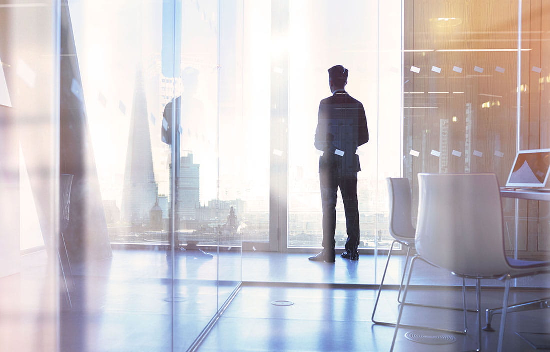 Businessman standing by a glass window in a corner office looking out the window at a city skyline.