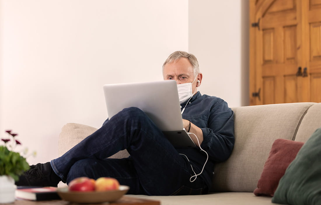 Man sitting on the couch wearing a mask on his laptop