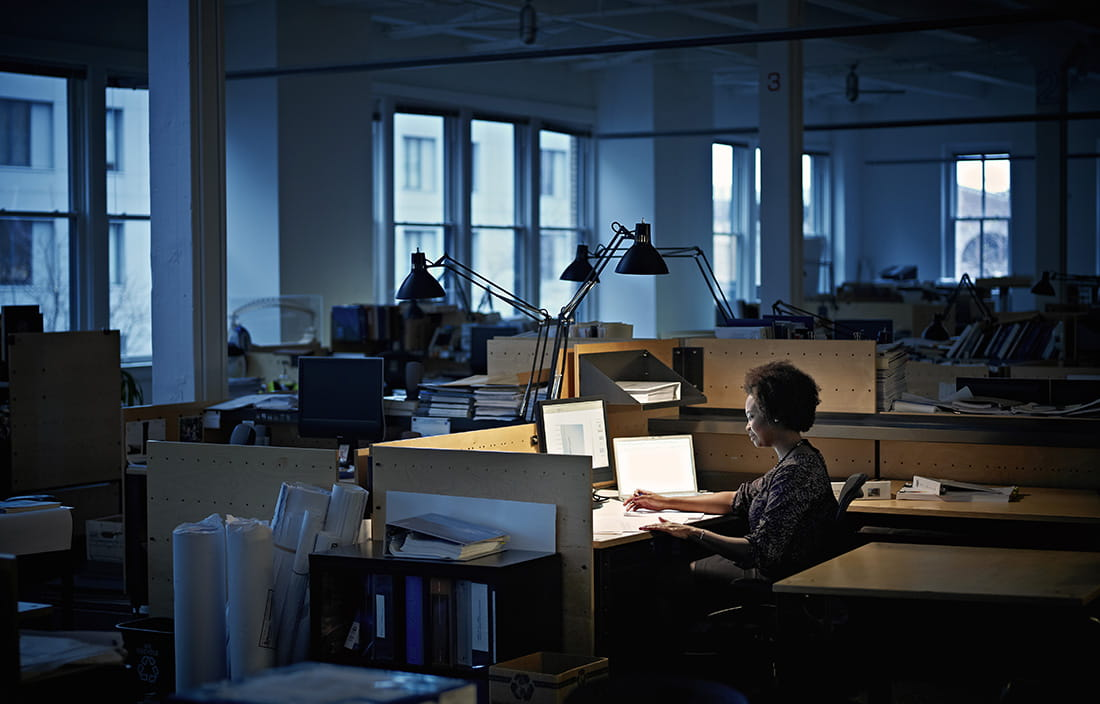 Woman sitting alone at her desk in a dark office
