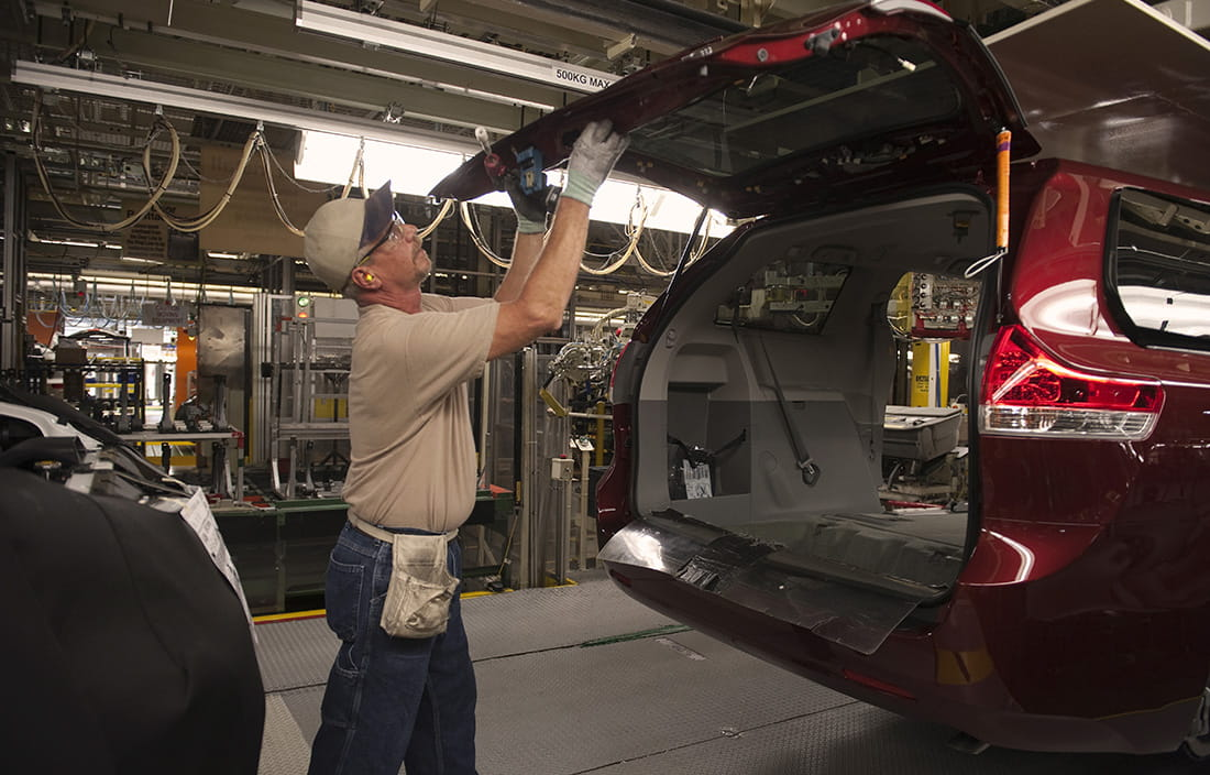 Automotive worker examining the back hatch of an SUV car.