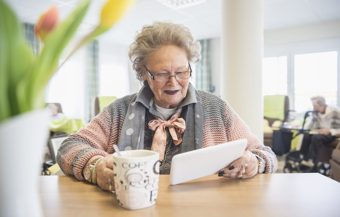 An elderly woman sitting at a table holding a coffee in one hand a tablet device in the other hand.