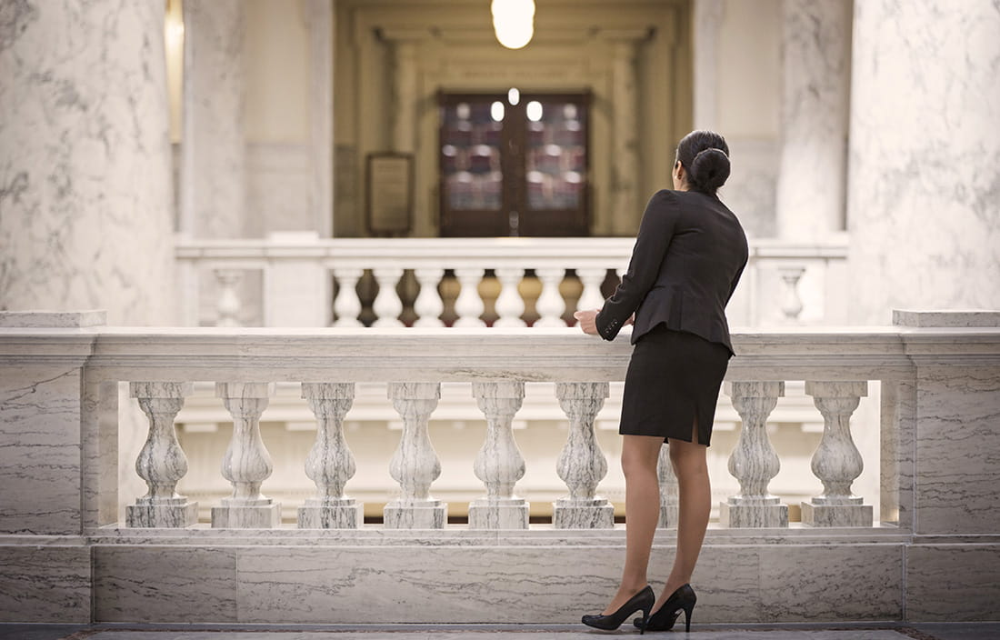 Businesswoman in a government building looking over a marble railing.
