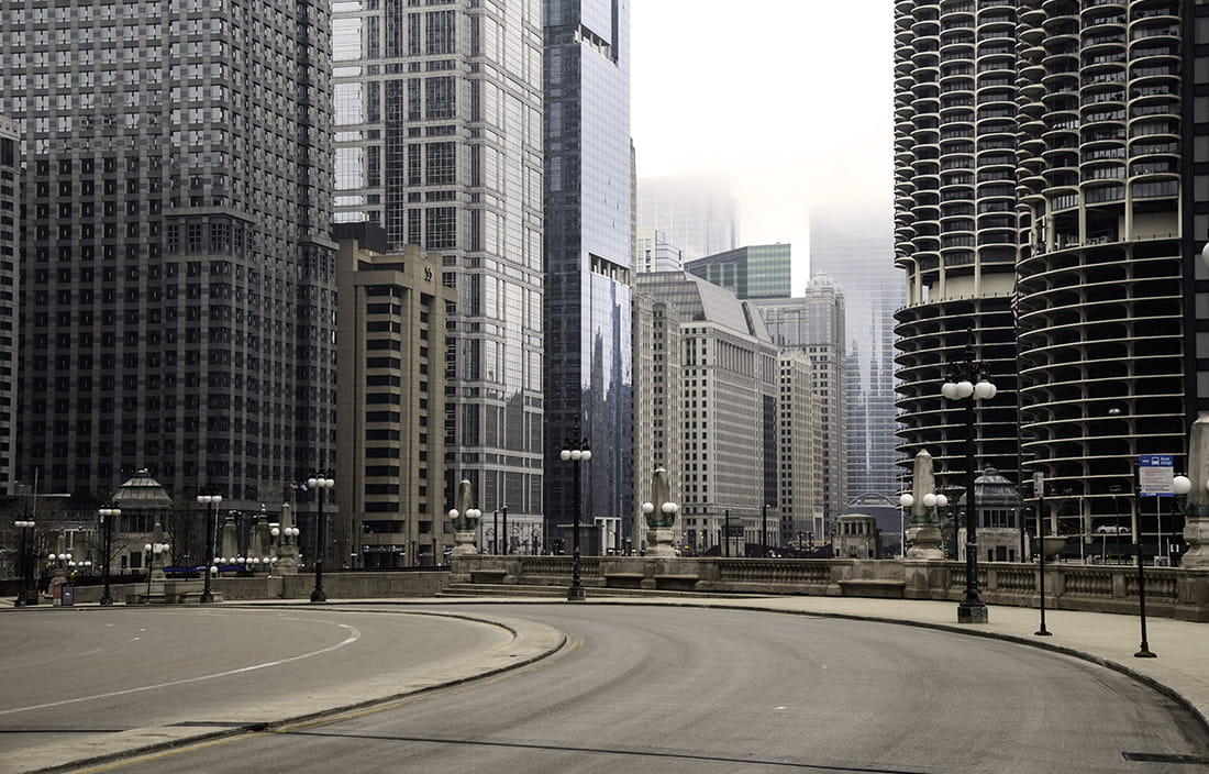 Photo of a left-hand turn for city-street road with city skyscrapers in the background.