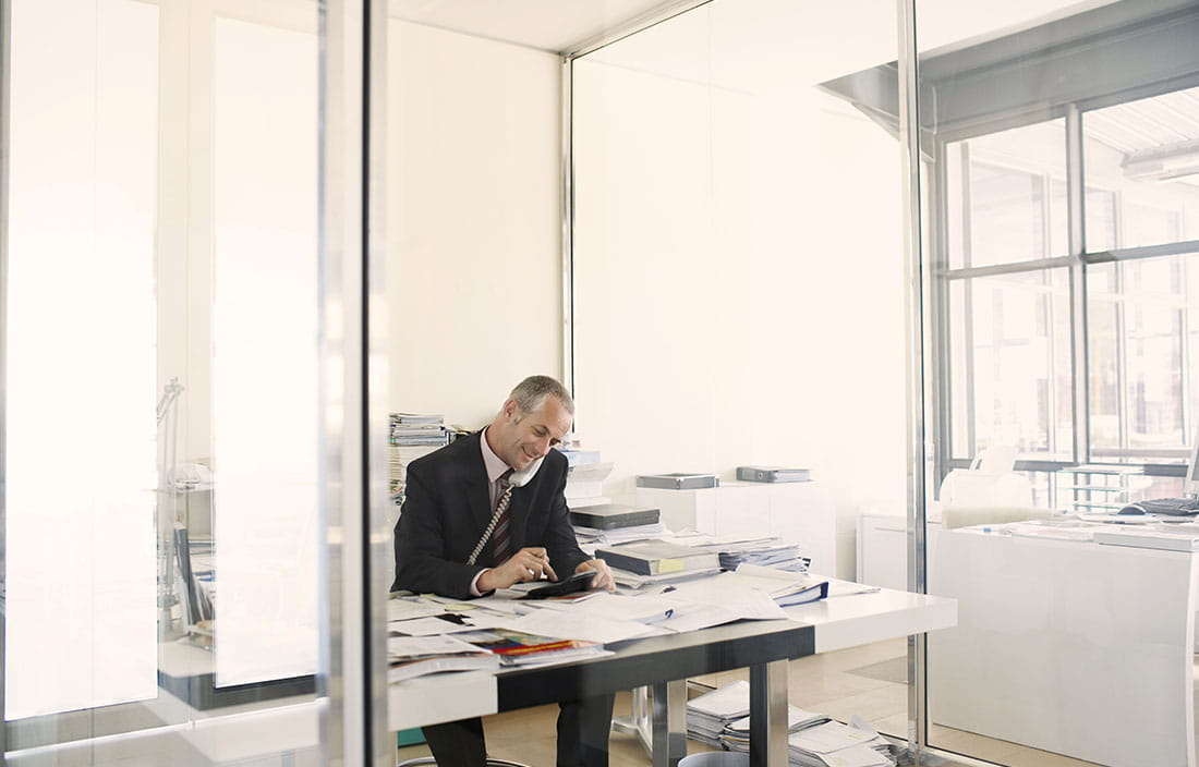 A CFO sitting at a desk taking a phone call.