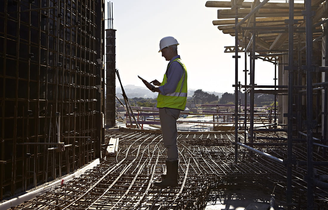 Construction worker outside on a tablet