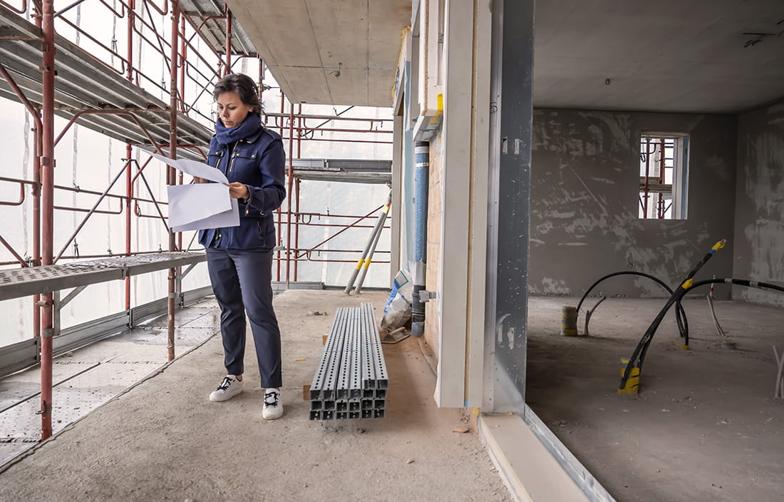 Woman standing at a construction site looking at blueprints