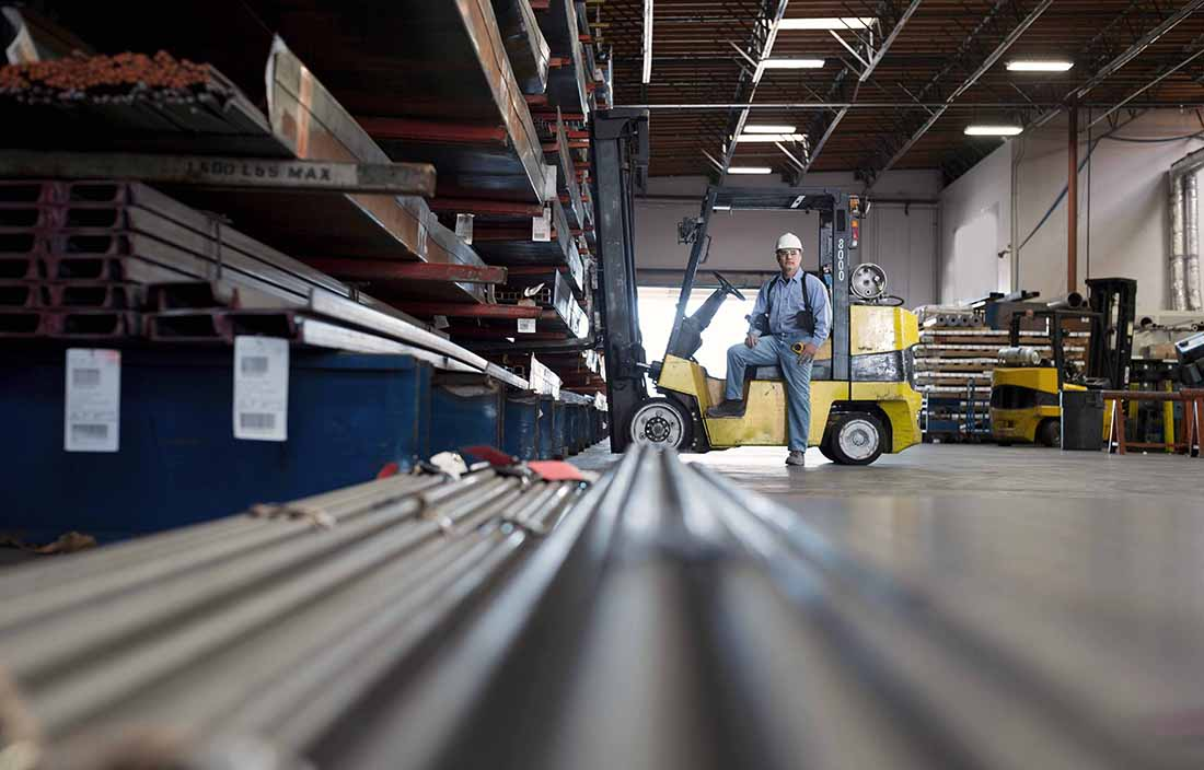 Auto worker driving a fork lift in a warehouse.
