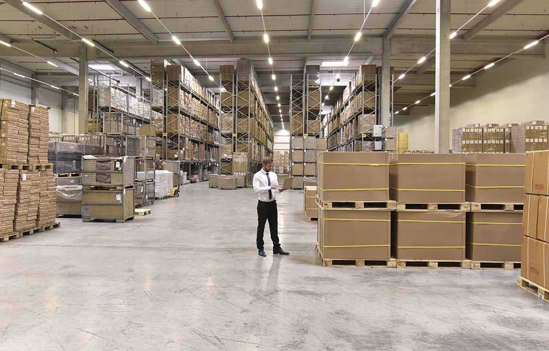 Man standing in a warehouse, checking stock