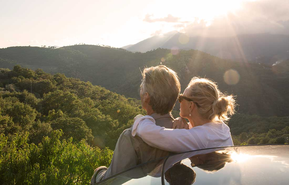 Man and woman sitting on the back of a car looking out at mountains