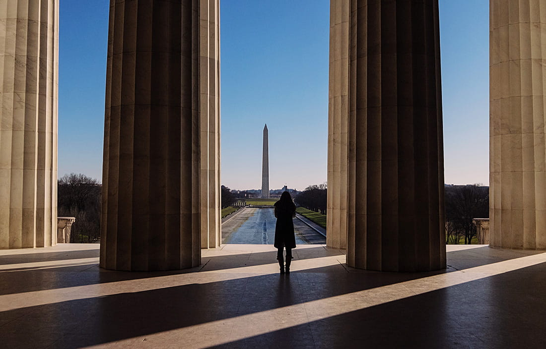 Woman standing by U.S. government building next to big pillars.