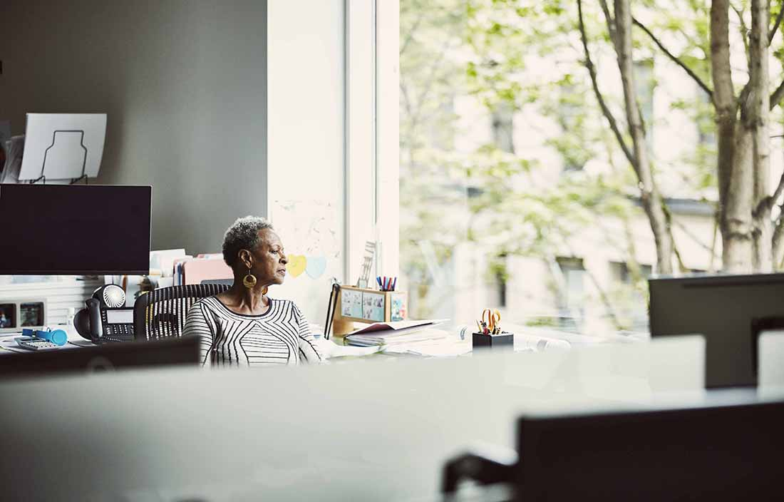 Elderly woman sitting in her home office looking out the window.